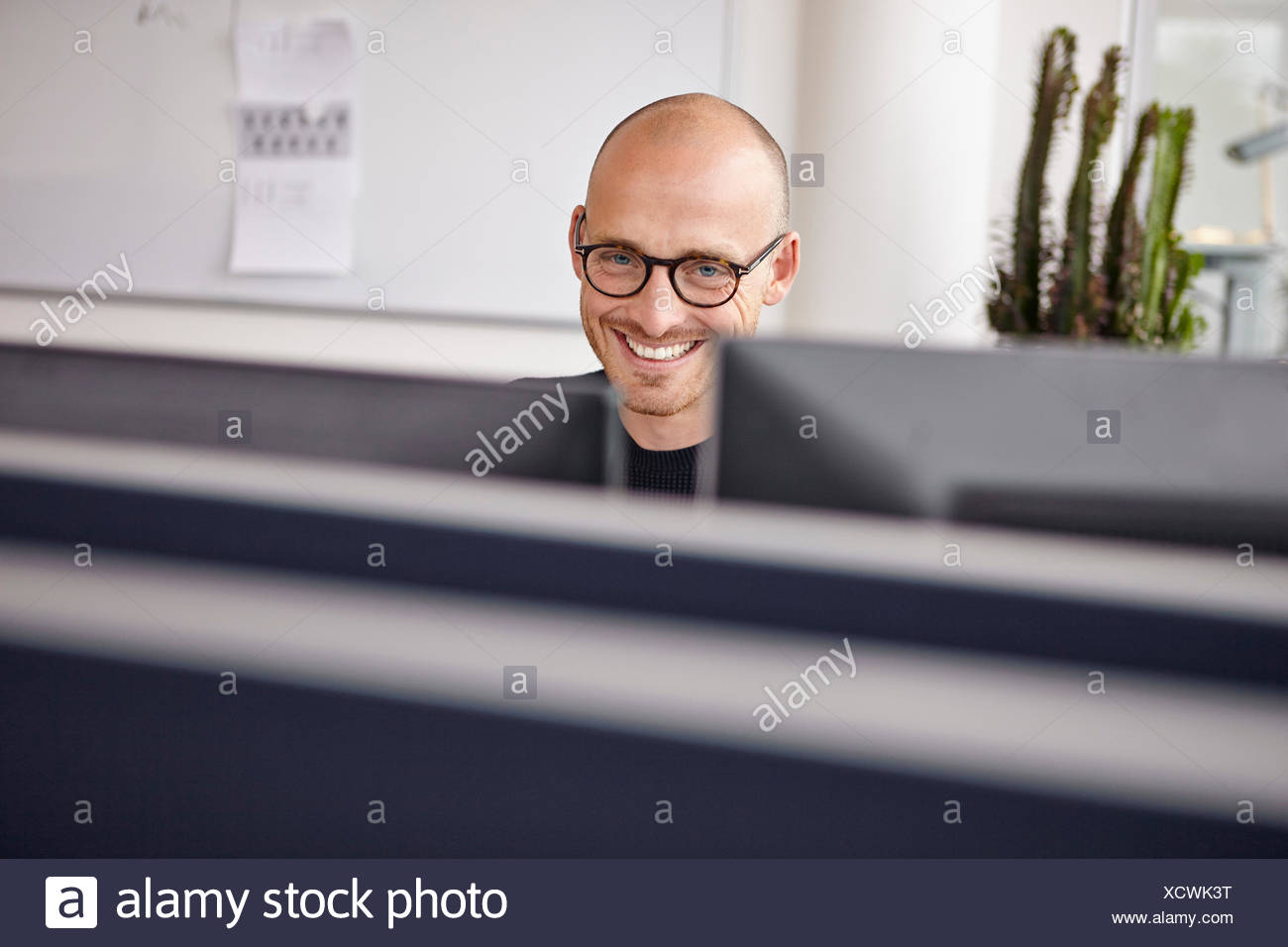 Smiling man in office behind computer screens - Stock Image