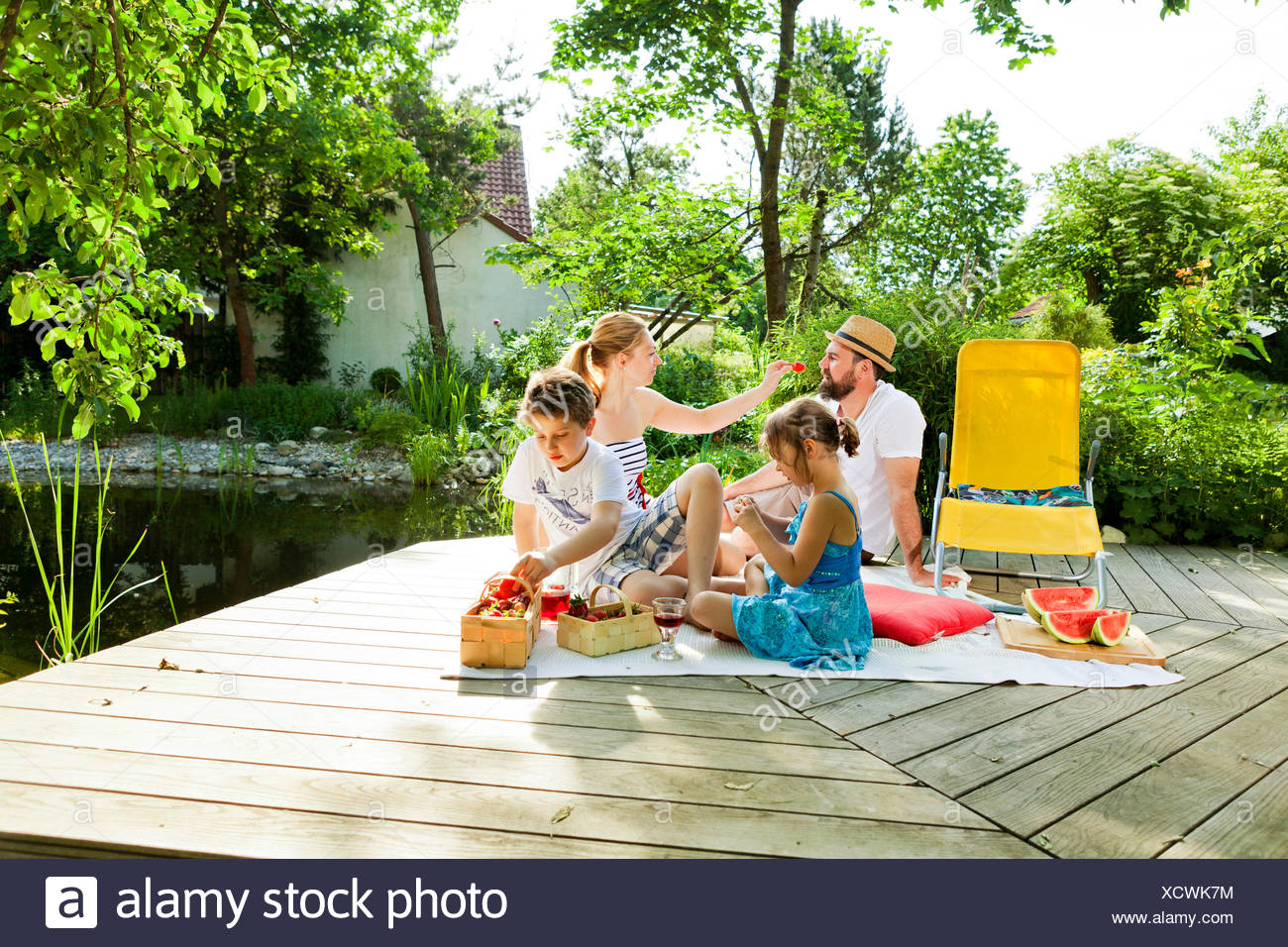 Family with two children having a picnic  by the pond, Munich, Bavaria, Germany - Stock Image