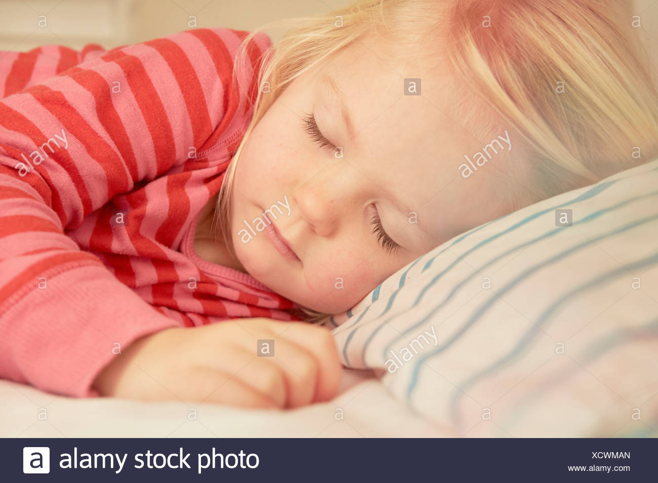 Young girl asleep in bed - Stock Image