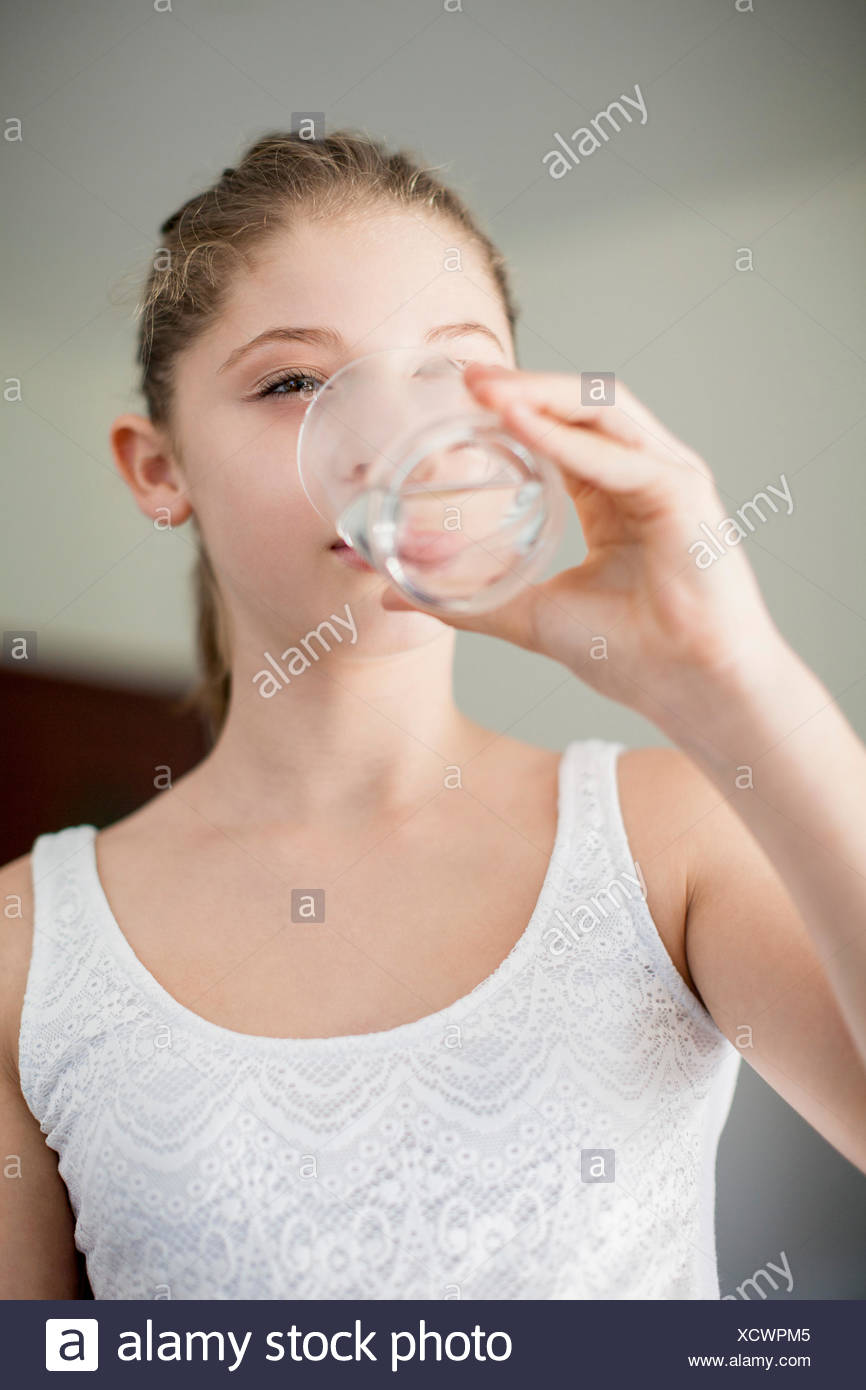 Girl drinking a glass of water - Stock Image