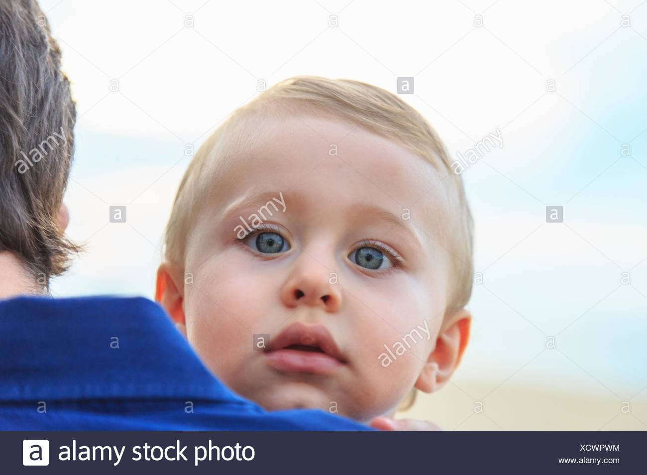 Baby boy looking over father's shoulder - Stock Image