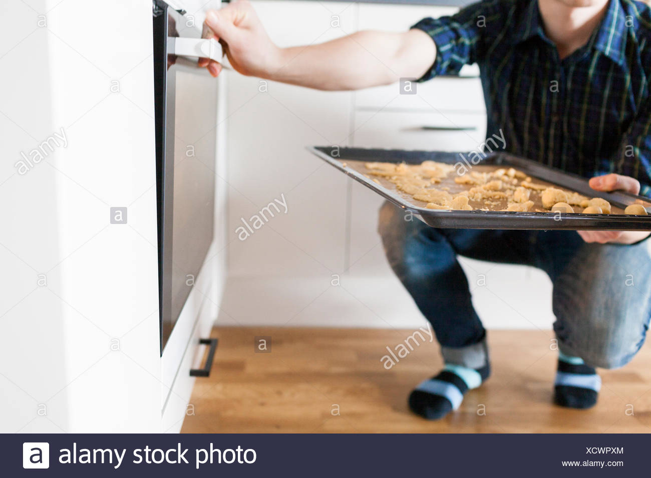 Low section of man putting baking tray in oven - Stock Image