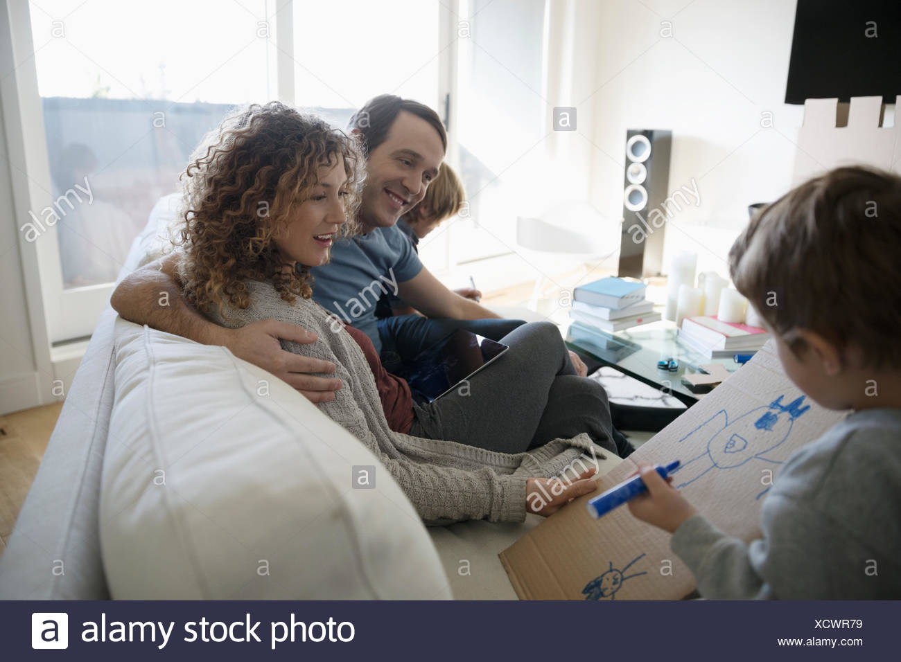 Family relaxing on sofa,son showing parents drawing on cardboard - Stock Image