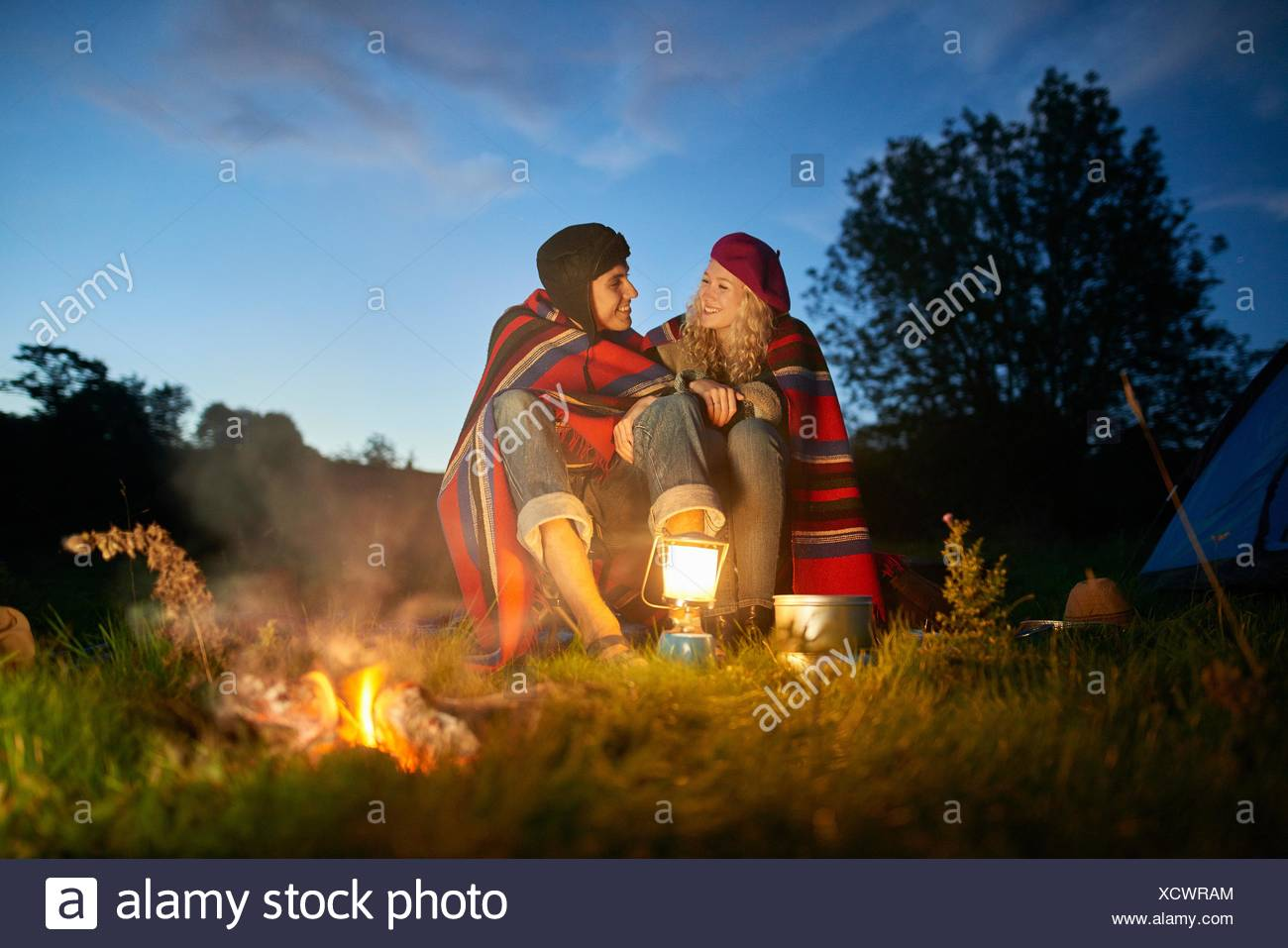 Young camping couple sitting by campfire at dusk - Stock Image