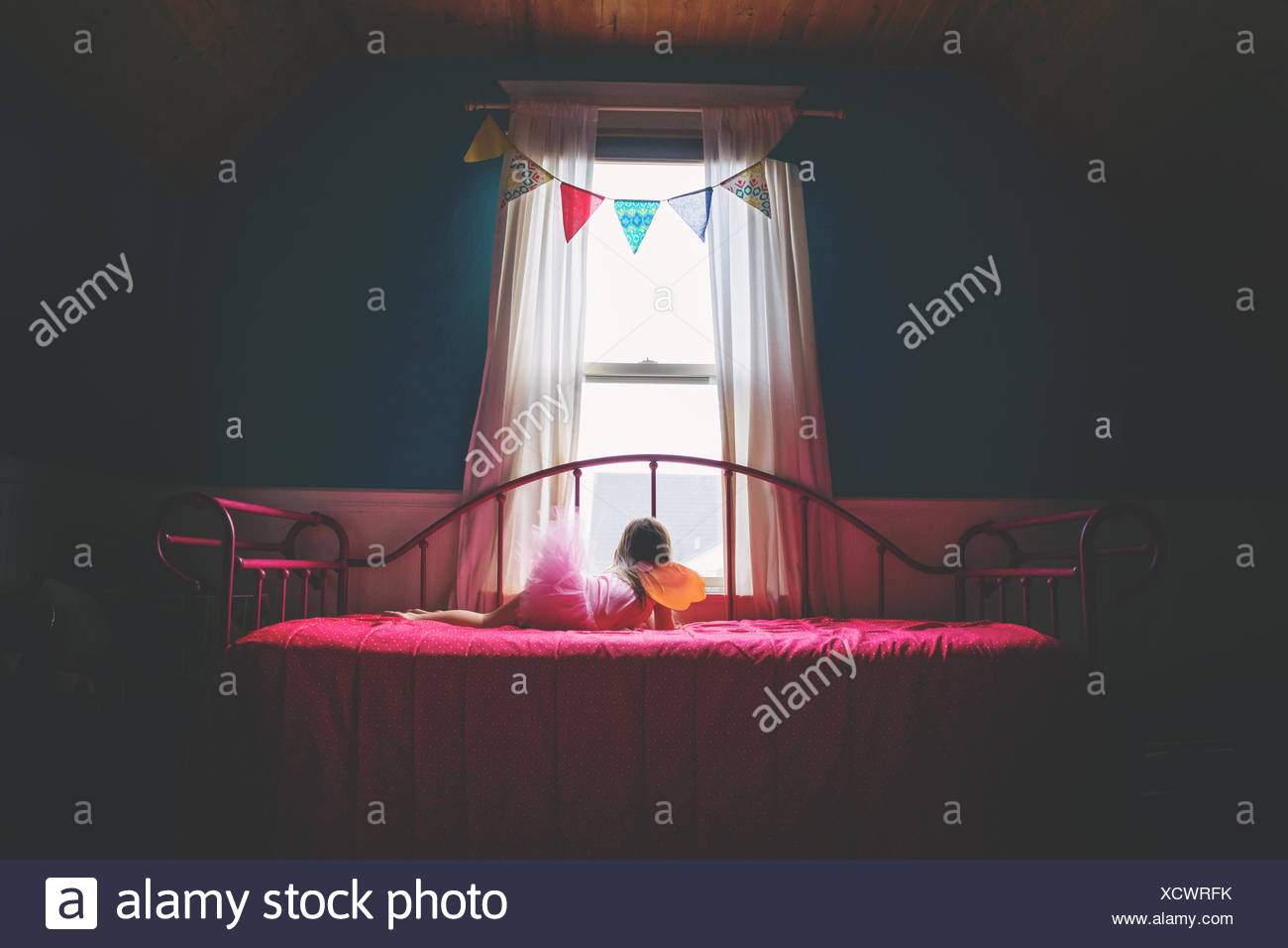 Girl lying on bed looking out of window - Stock Image