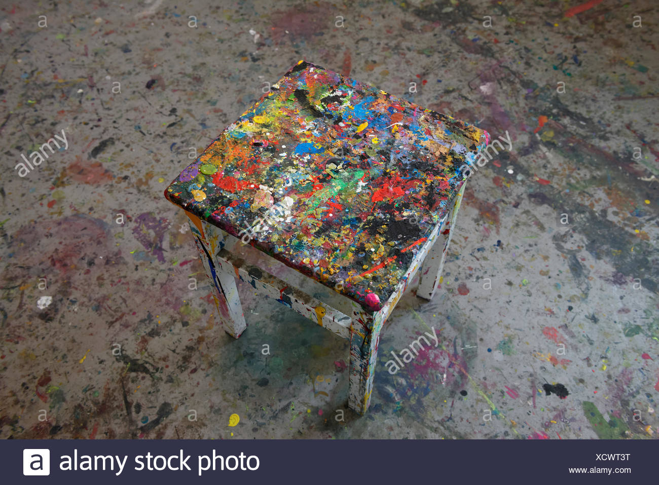Footstool with colorful paint residues in a studio, Germany - Stock Image