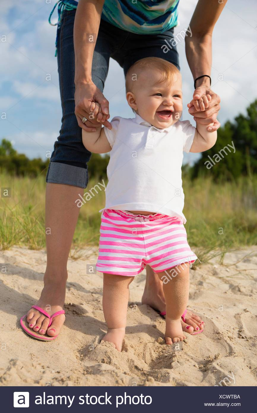 Mid adult woman holding baby daughters hands while toddling in sand - Stock Image