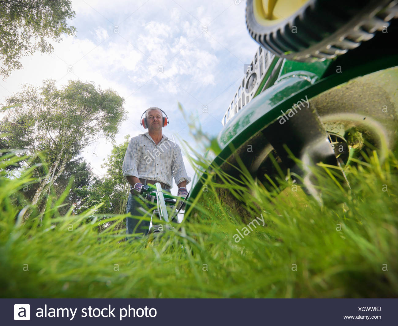 Low angle view of man mowing lawn - Stock Image