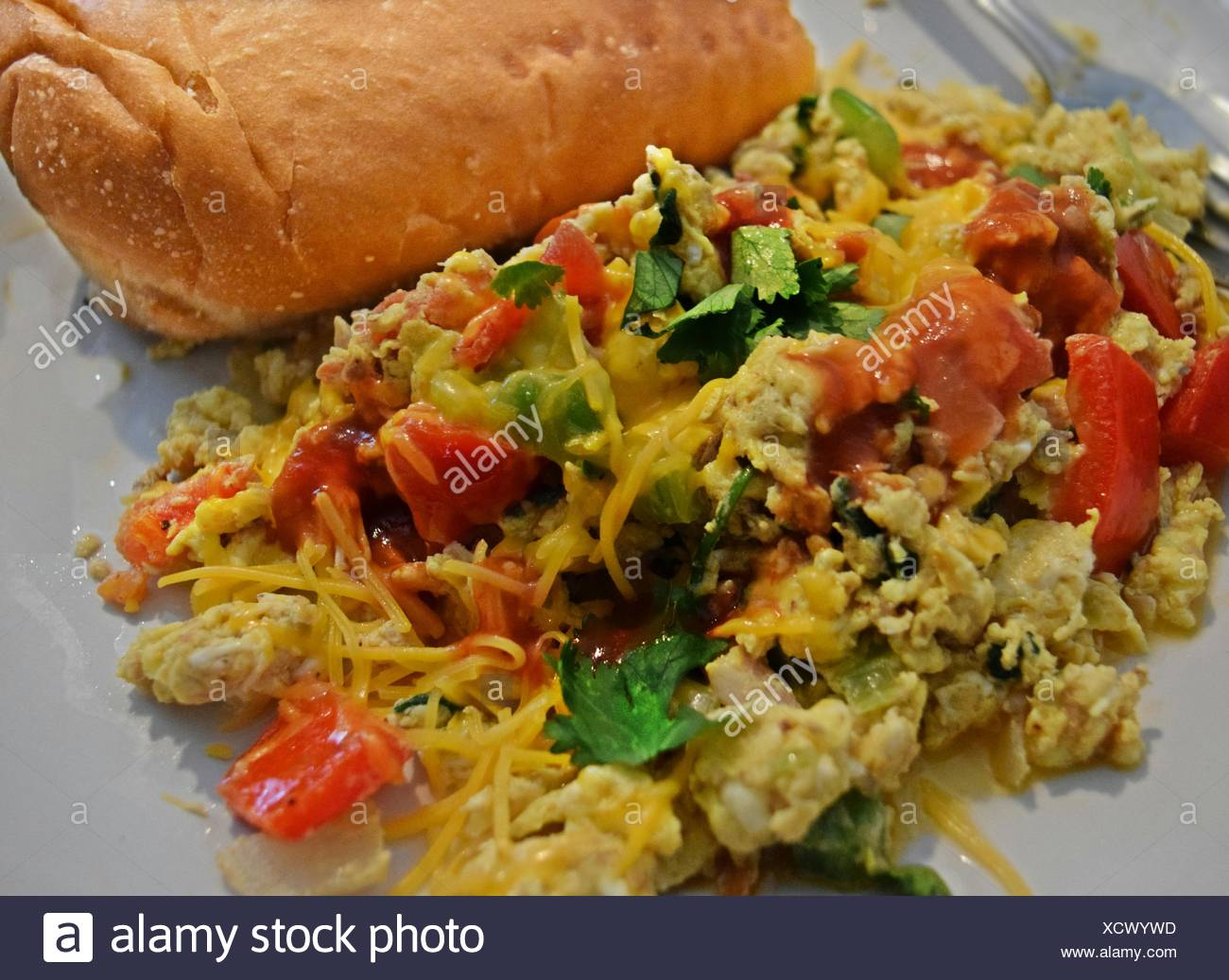 Close-Up Of Omelet With Vegetables And Bun On Plate - Stock Image