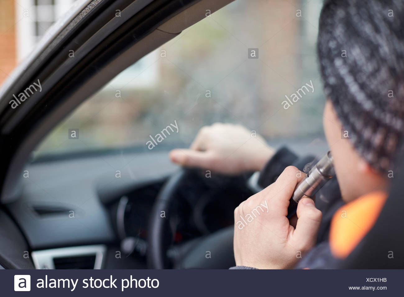 Close Up Of Young Man Sitting In Car Using Vapourizer - Stock Image