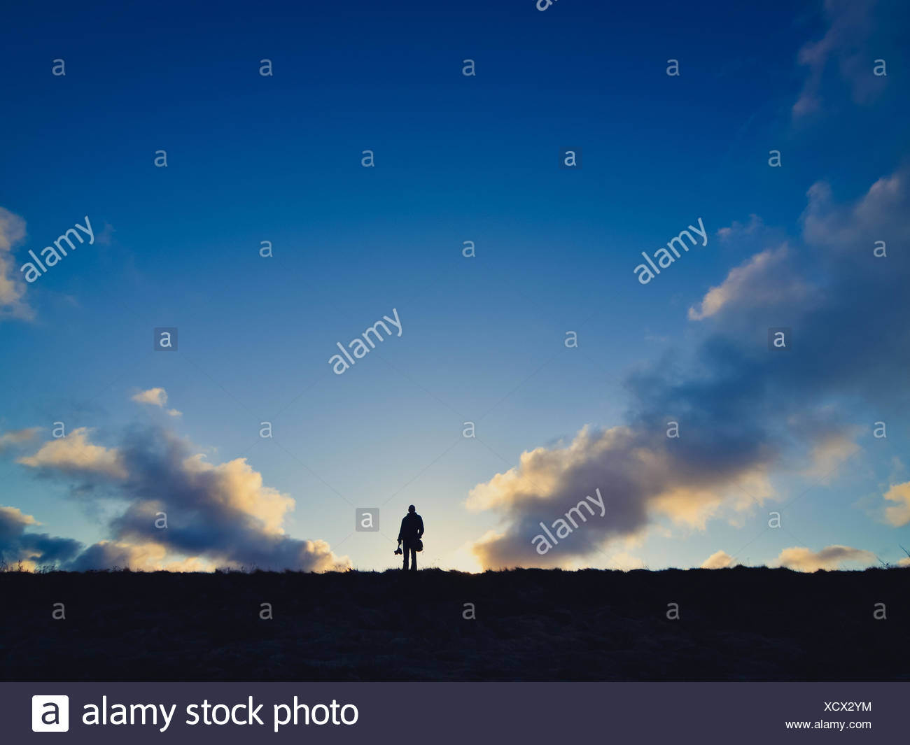 Distant View Of Silhouette Man On Field Against Sky At Sunset - Stock Image