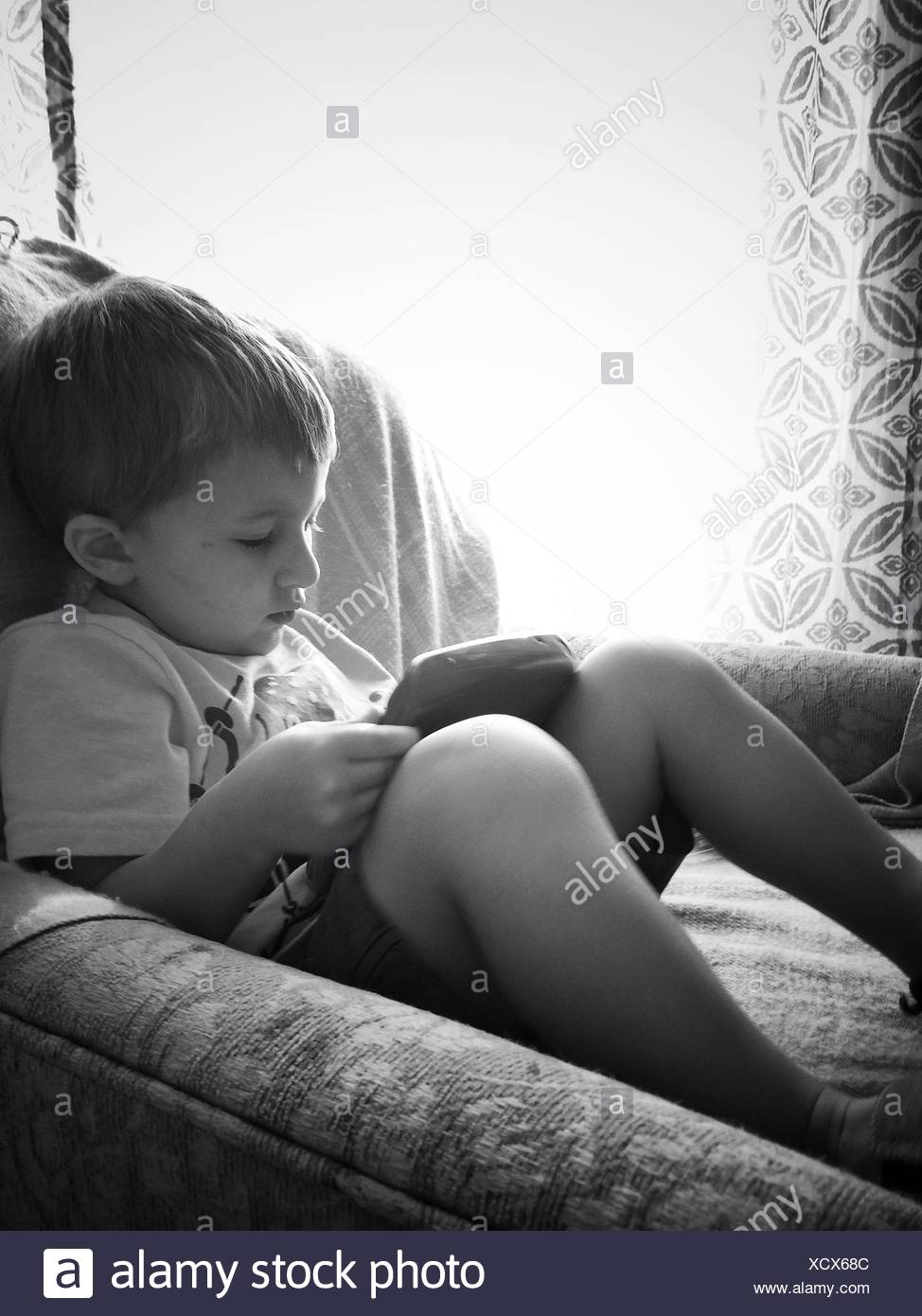 Boy Sitting On Sofa Besides Window At Home - Stock Image