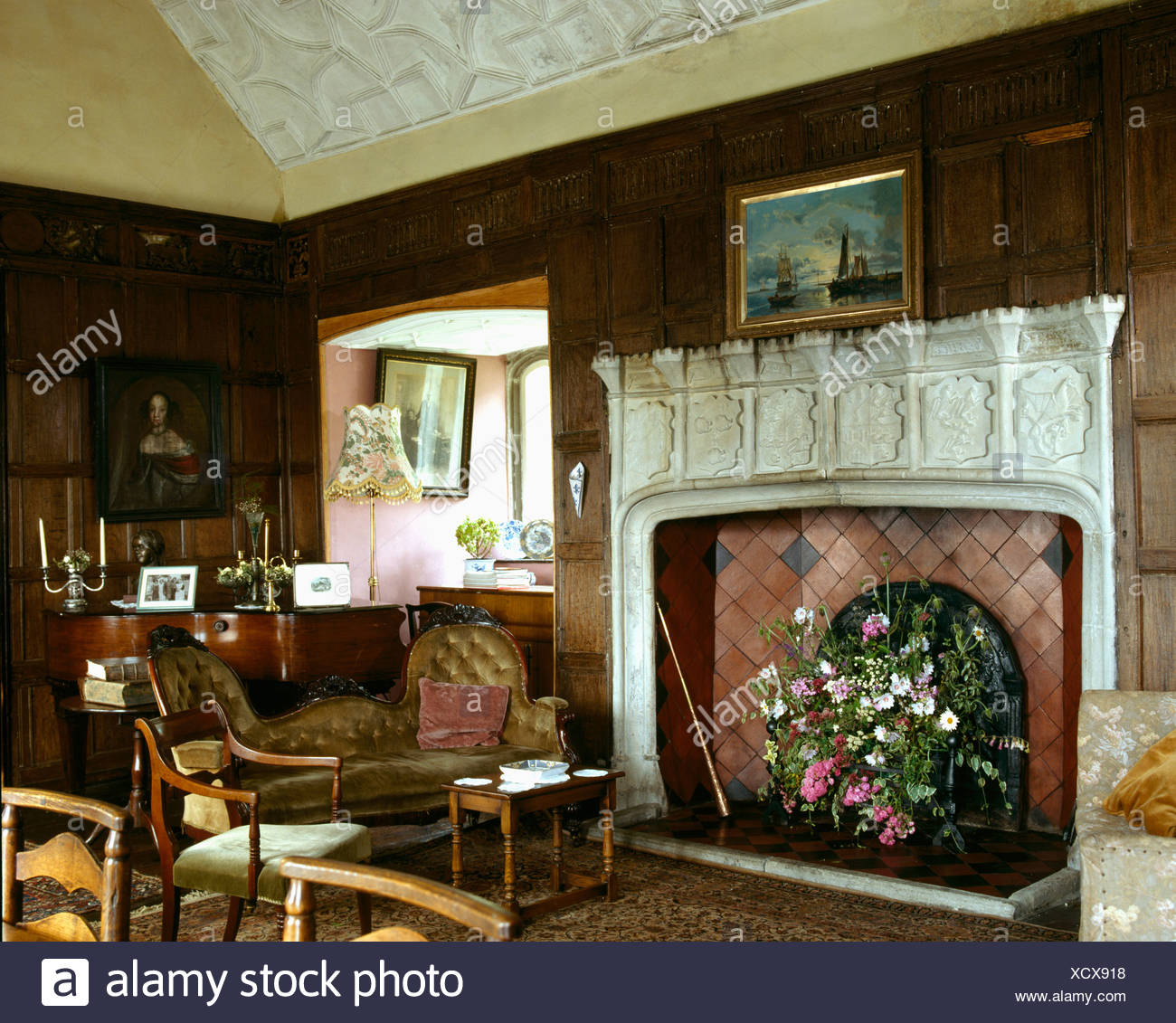 Carved stone fireplace in panelled country sitting room - Stock Image