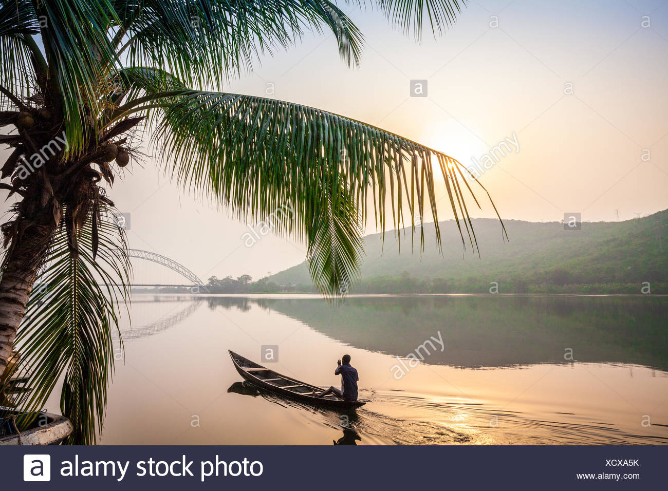 Local paddling in wooden canoe, Volta River, Ghana, Africa - Stock Image