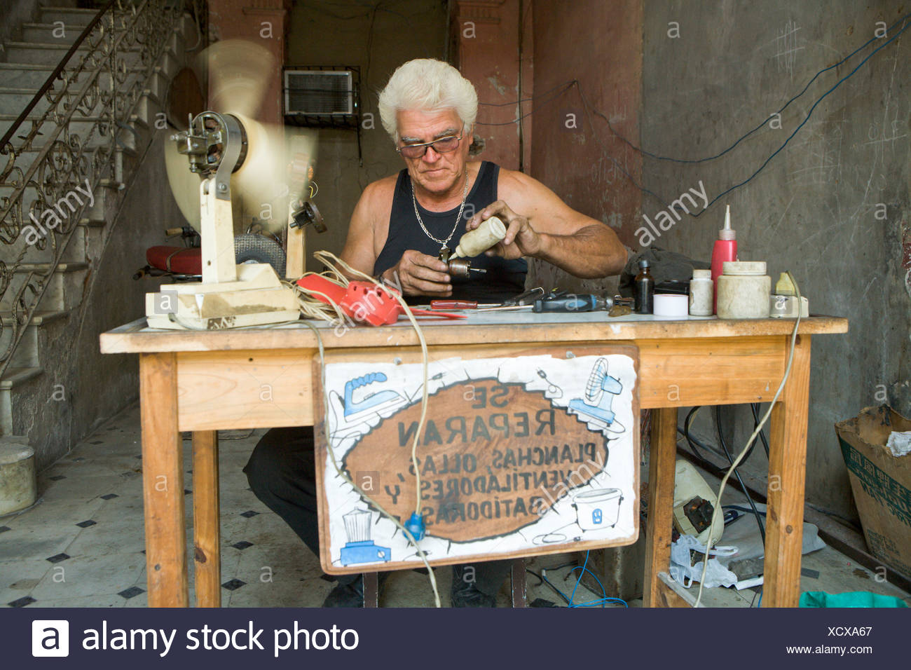Small businessman, a repair service for household goods and electrical appliances such as irons, fans, pots, blenders Stock Photo