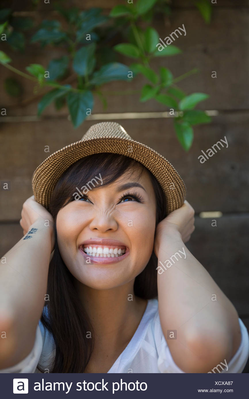 Portrait enthusiastic woman with black hair wearing hat - Stock Image
