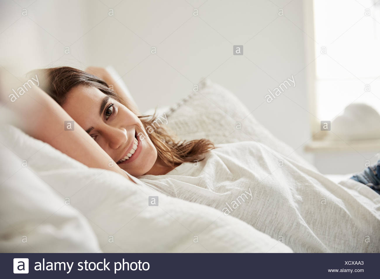 Surface level portrait of beautiful young woman lying on bed - Stock Image