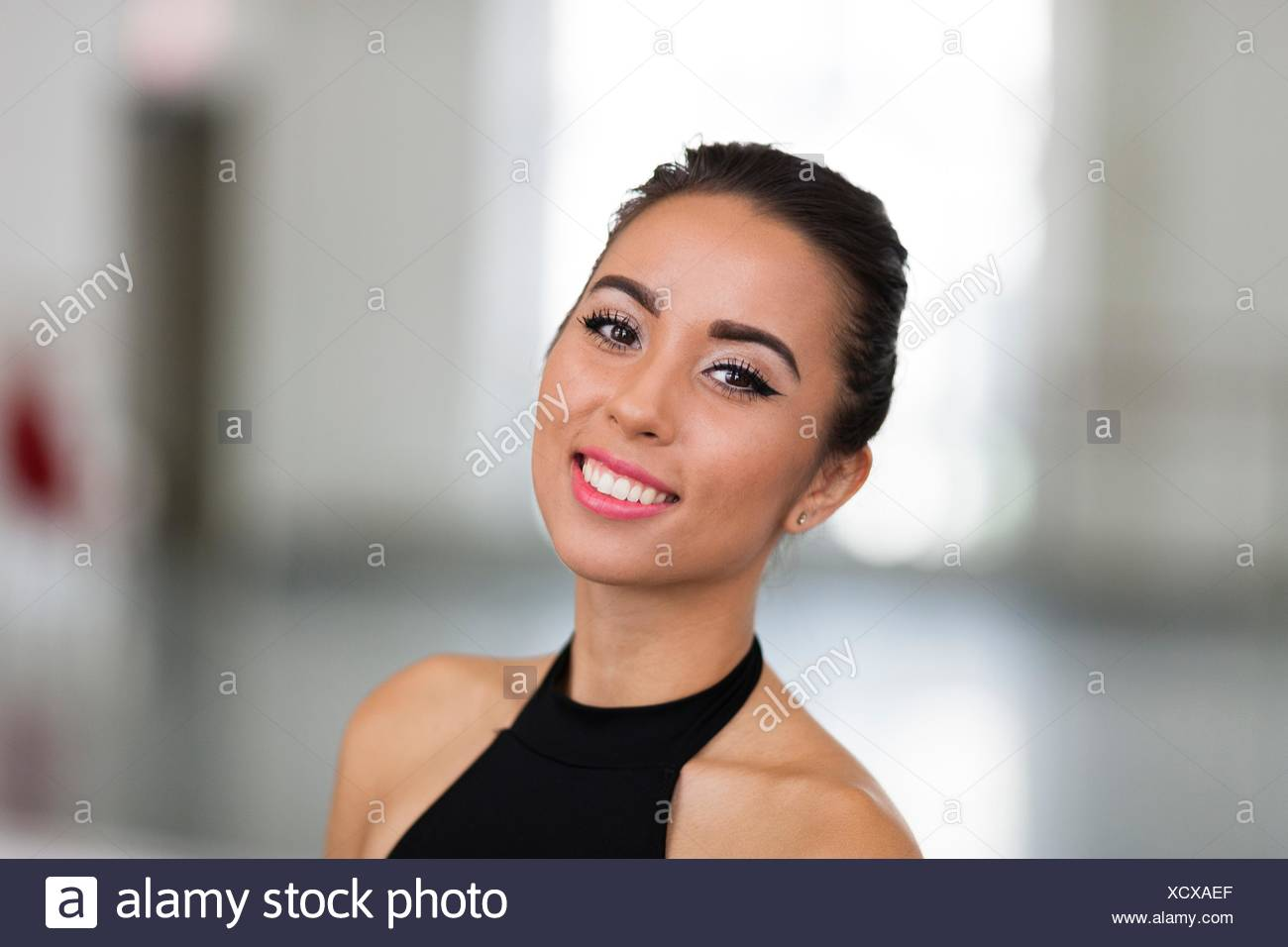 Portrait of young woman with bare shoulders looking at camera smiling - Stock Image