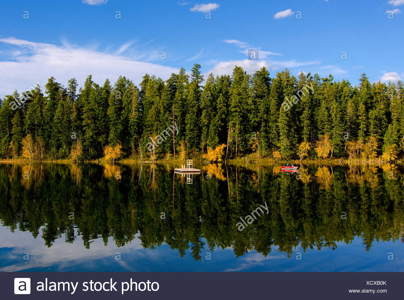 Boaters enjoy the early fall colours surrounding Gardom Lake, near Salmon Arm, in British Columbia's Shuswap Region, Canada. - Stock Image