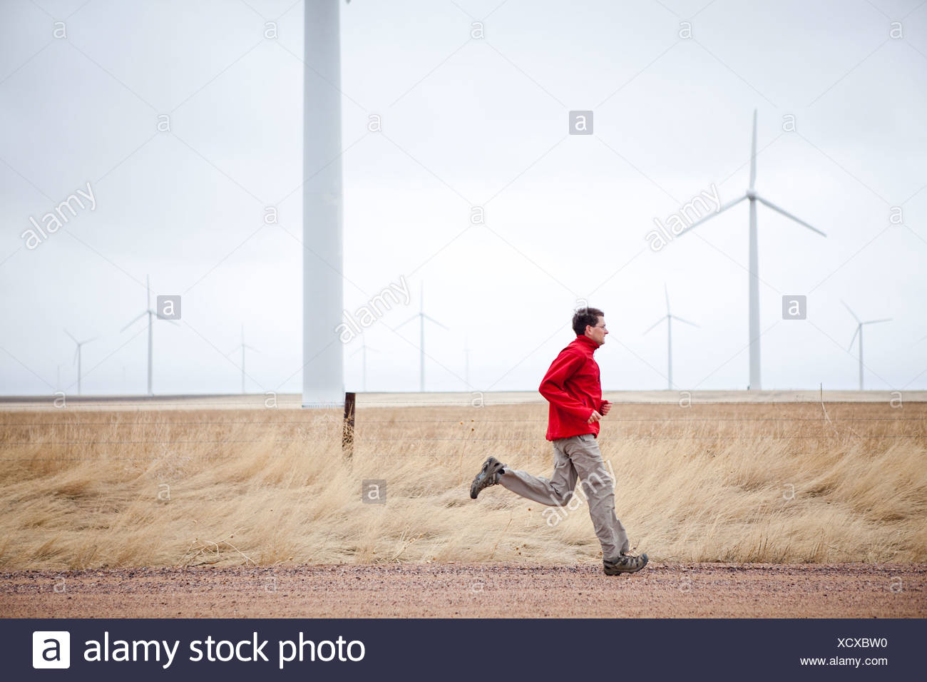 A man runs down a dirt road with windmills in the background, in the Pawnee Grasslands, Colorado. - Stock Image