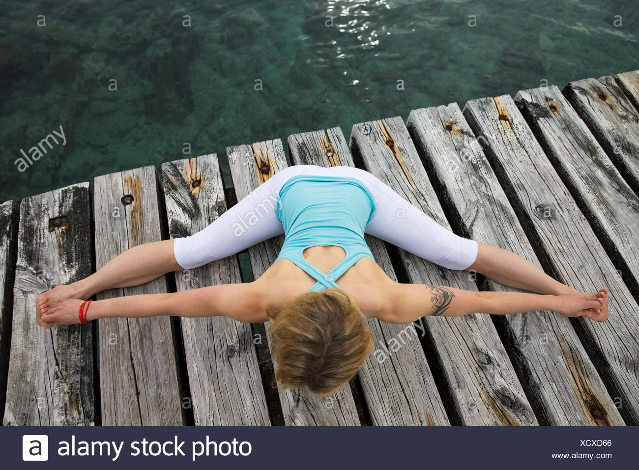 Overhead view of mid adult woman with arms and legs outstretched practicing yoga on wooden sea pier - Stock Image
