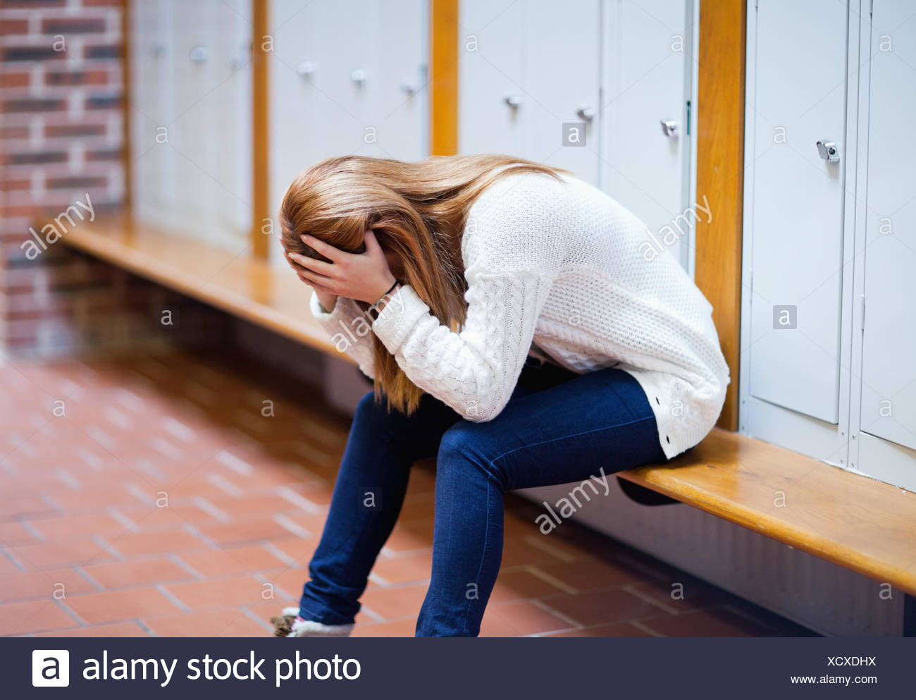 Depressed student sitting on a bench - Stock Image