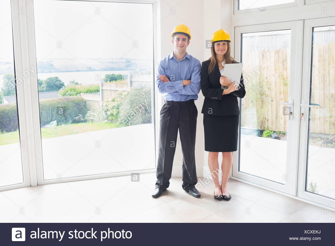 Estate agent and client wearing hardhats - Stock Image