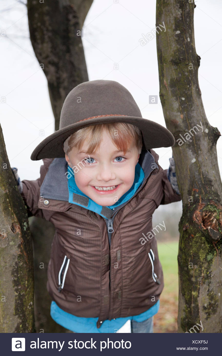 High-spirited boy, 5, wearing a hat, on a tree Stock Photo