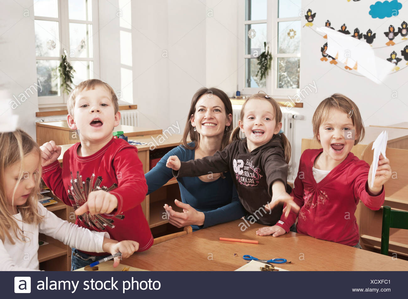 Children In Nursery School Throwing Paper Planes In The Air, Kottgeisering, Bavaria, Germany, Europe Stock Photo