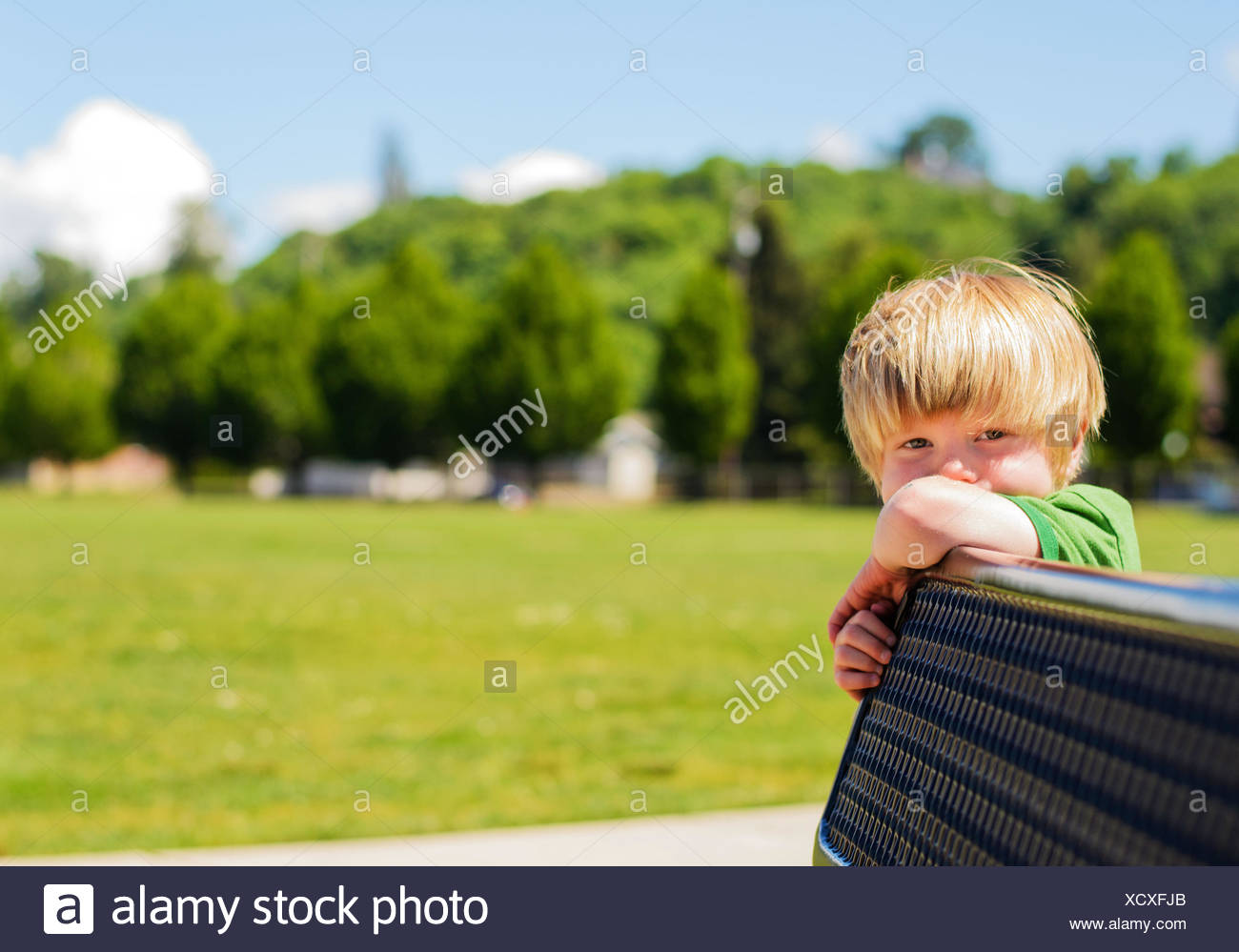 Boy leaning on bench (4-5 years) - Stock Image