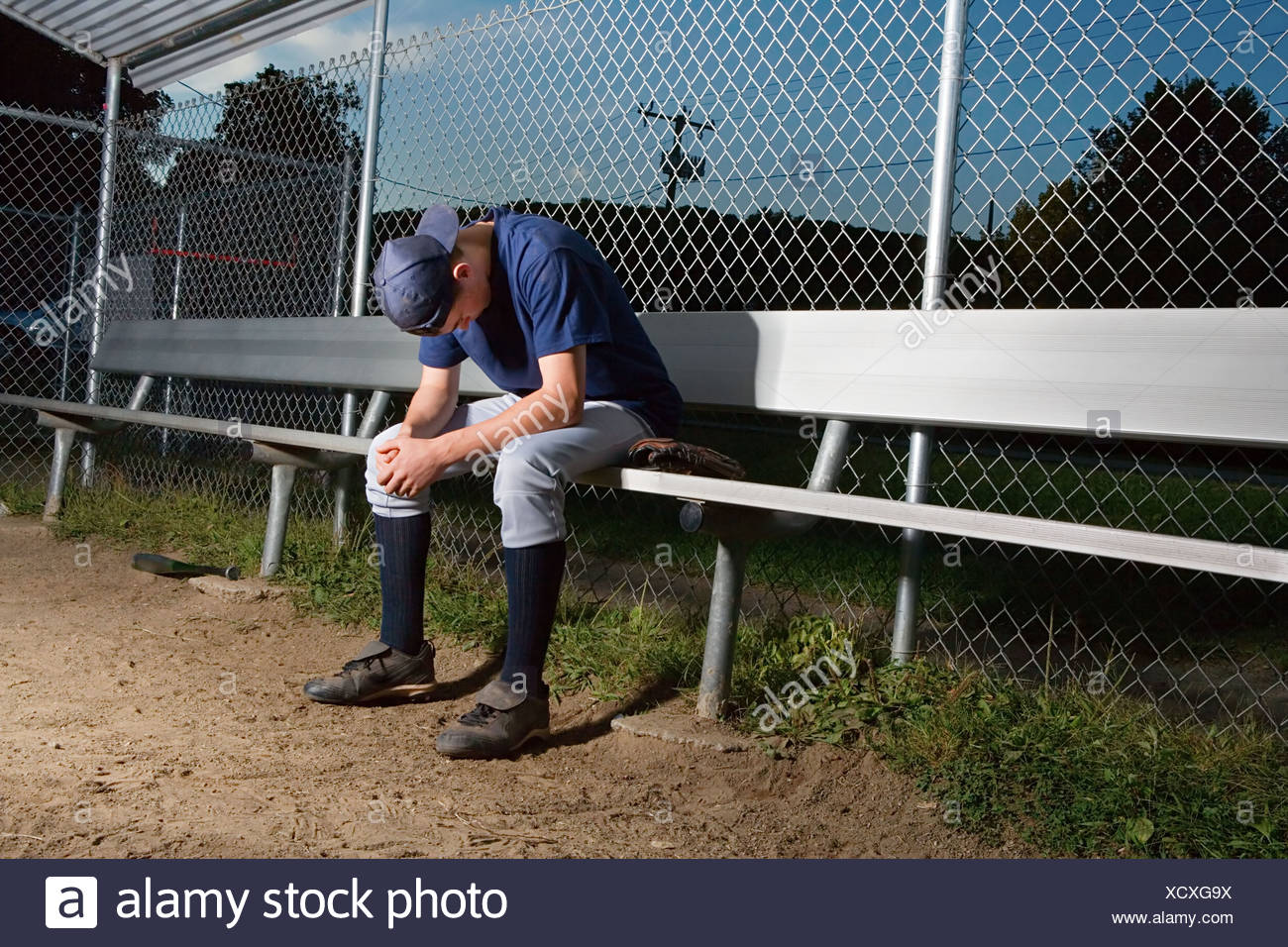 Teenage boy watching from the sidelines - Stock Image