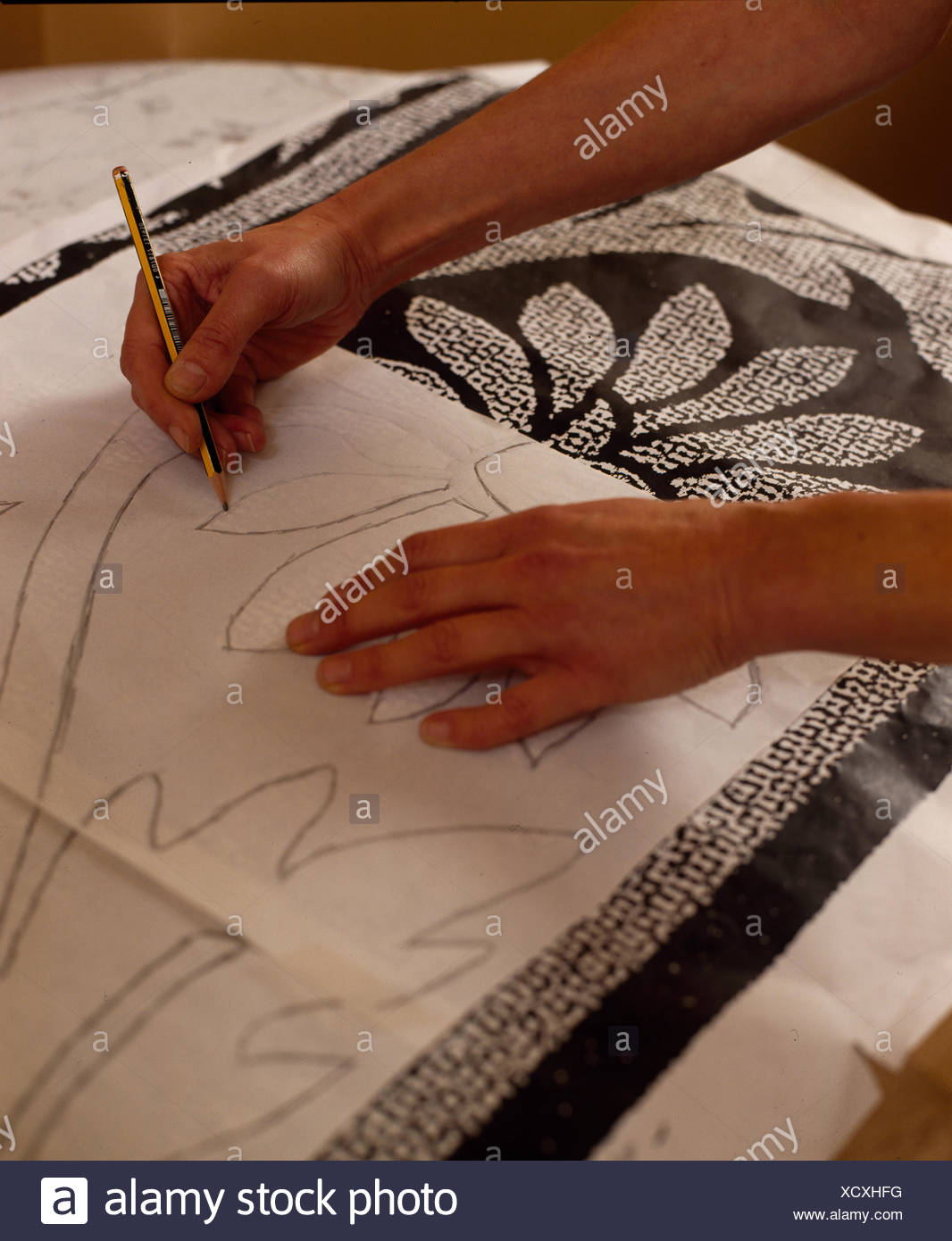 Close-up of hands tracing pattern - Stock Image