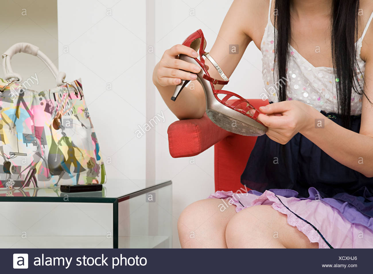 Woman holding a high heeled shoe - Stock Image