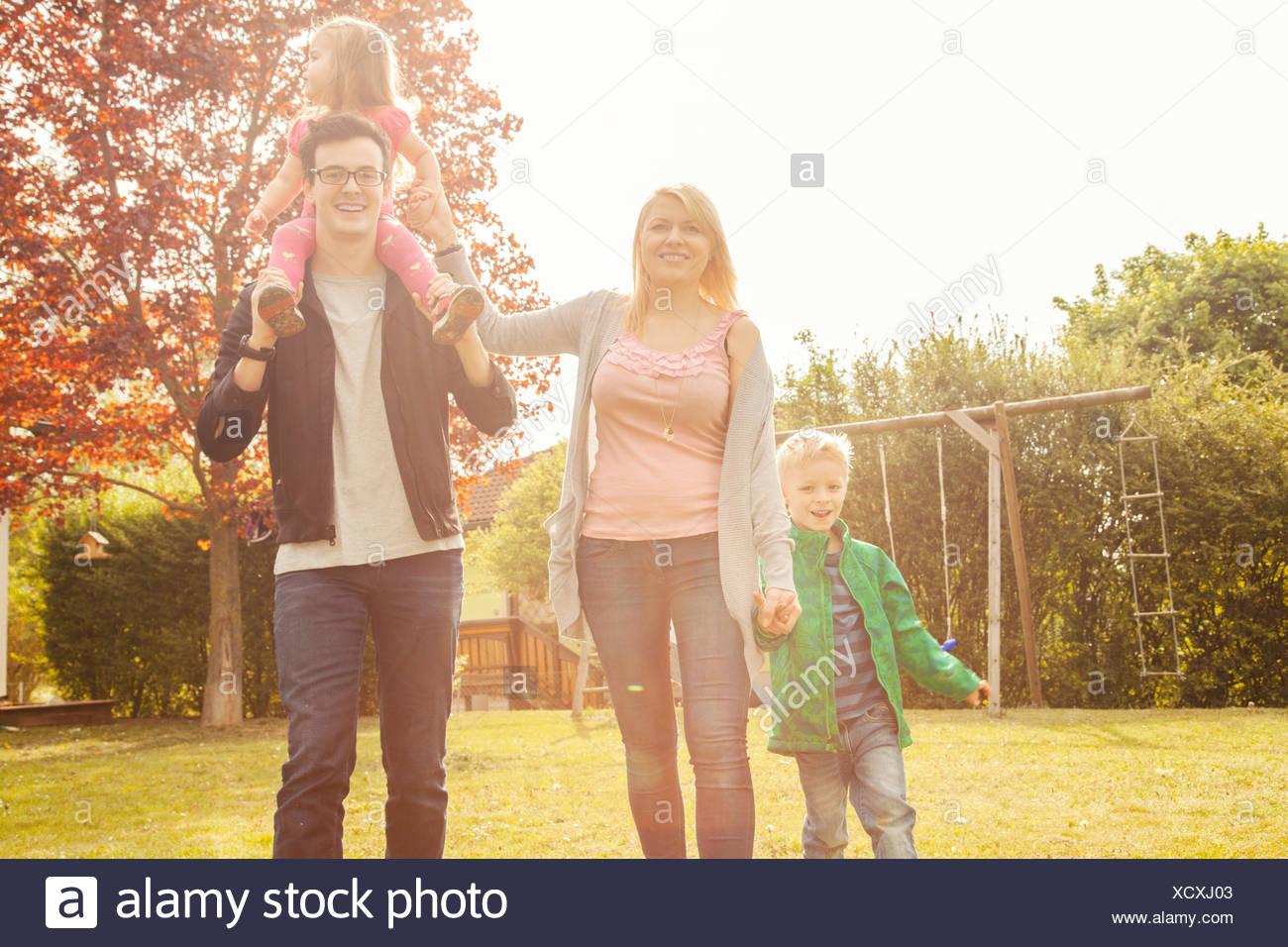 Family in garden, swings in background - Stock Image