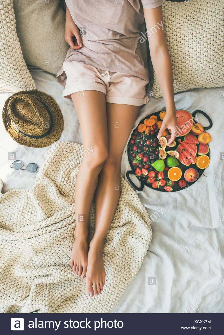 Summer healthy raw vegan clean eating breakfast in bed concept. Young girl wearing pastel colored home clothes taking fruit from tray full of fresh se - Stock Image
