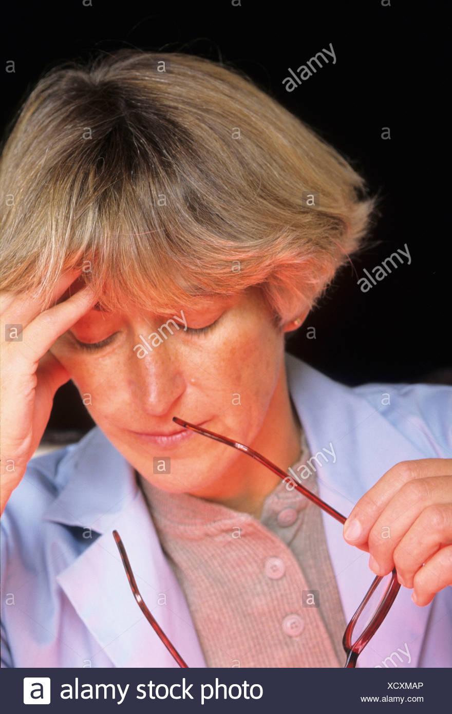 FEMALE PHYSICIAN WITH HEADACHE OR FATIGUED - Stock Image