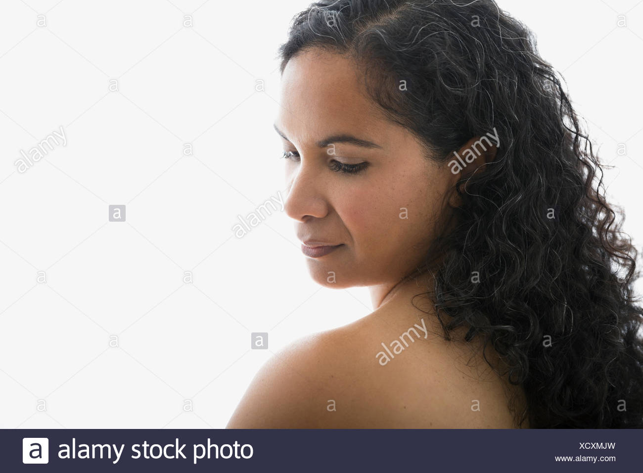 Woman with curly hair looking down at shoulder - Stock Image