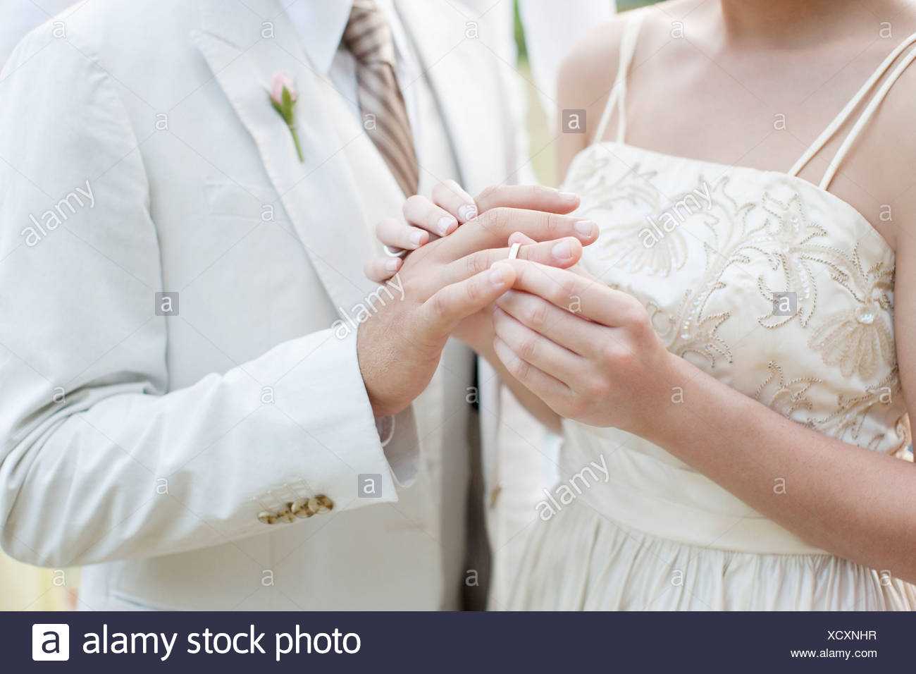 Bride putting ring on groom's finger - Stock Image
