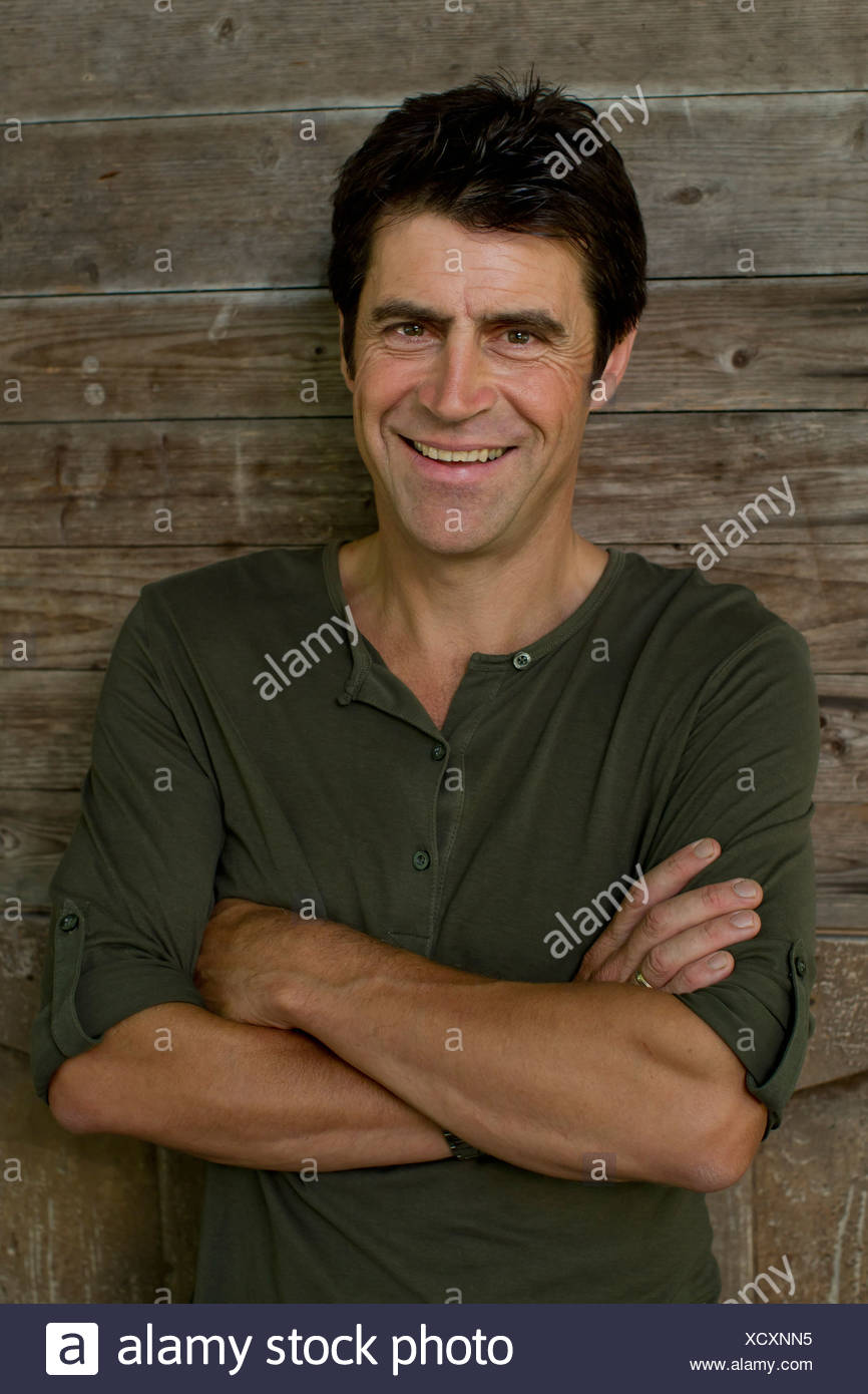557f2e5168a Portrait of mature man leaning against garden shed - Stock Image
