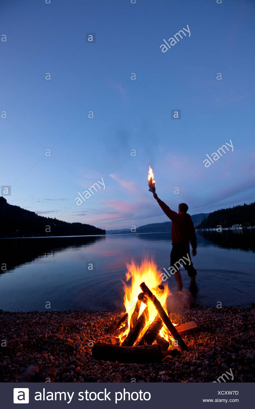 Lone figure stands behind campfire in Idaho. - Stock Image