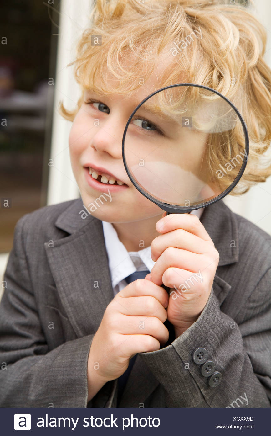 Boy using magnifying glass outdoors Stock Photo