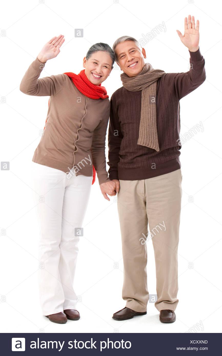 Senior couple waving hands - Stock Image
