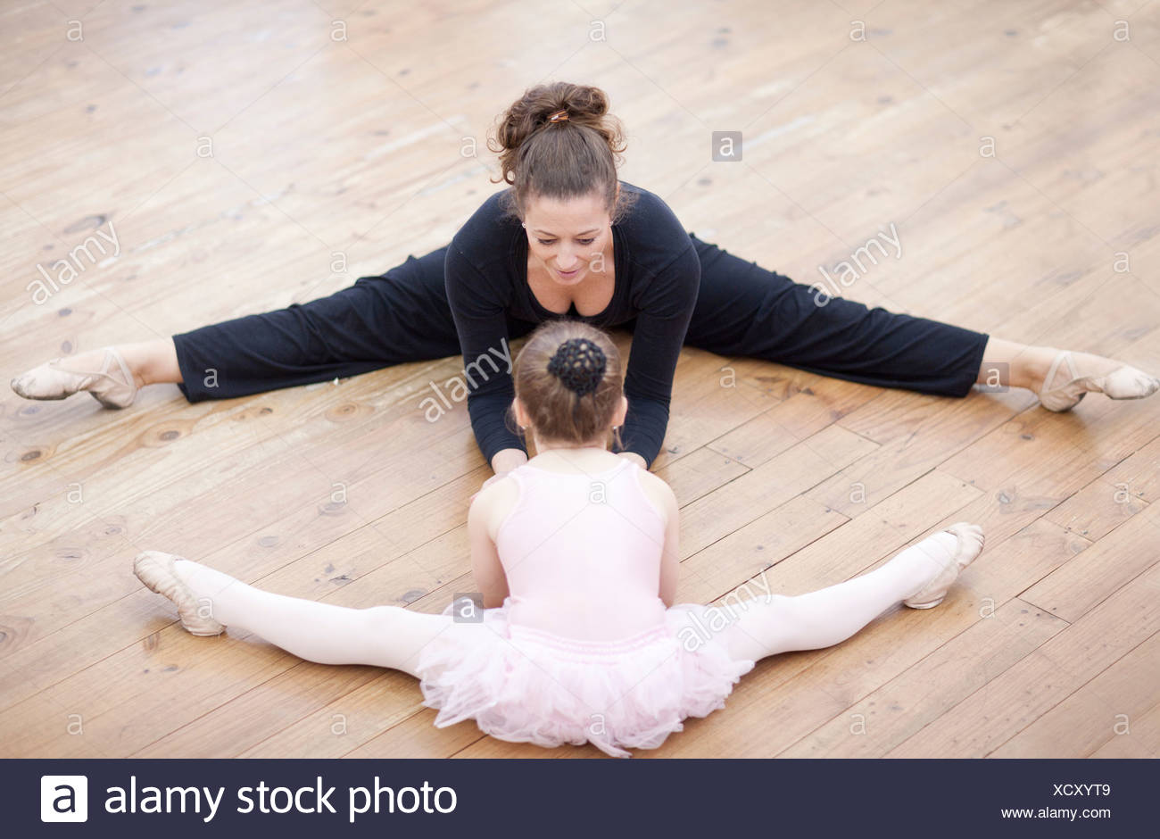 Teacher and young ballerina practicing stretch - Stock Image