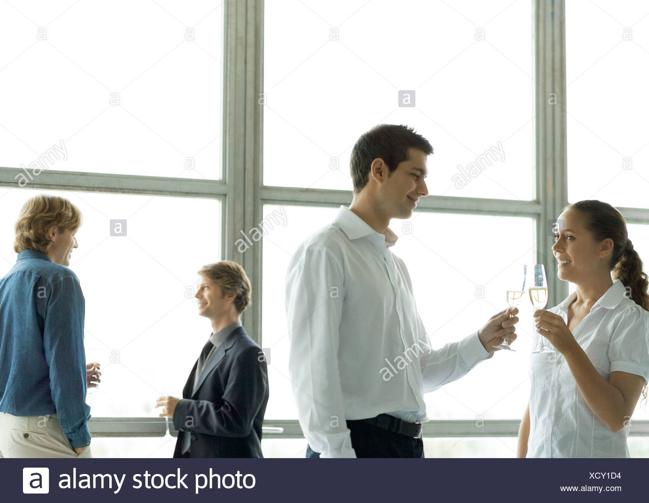 People talking during office party, holding glasses of champagne - Stock Image