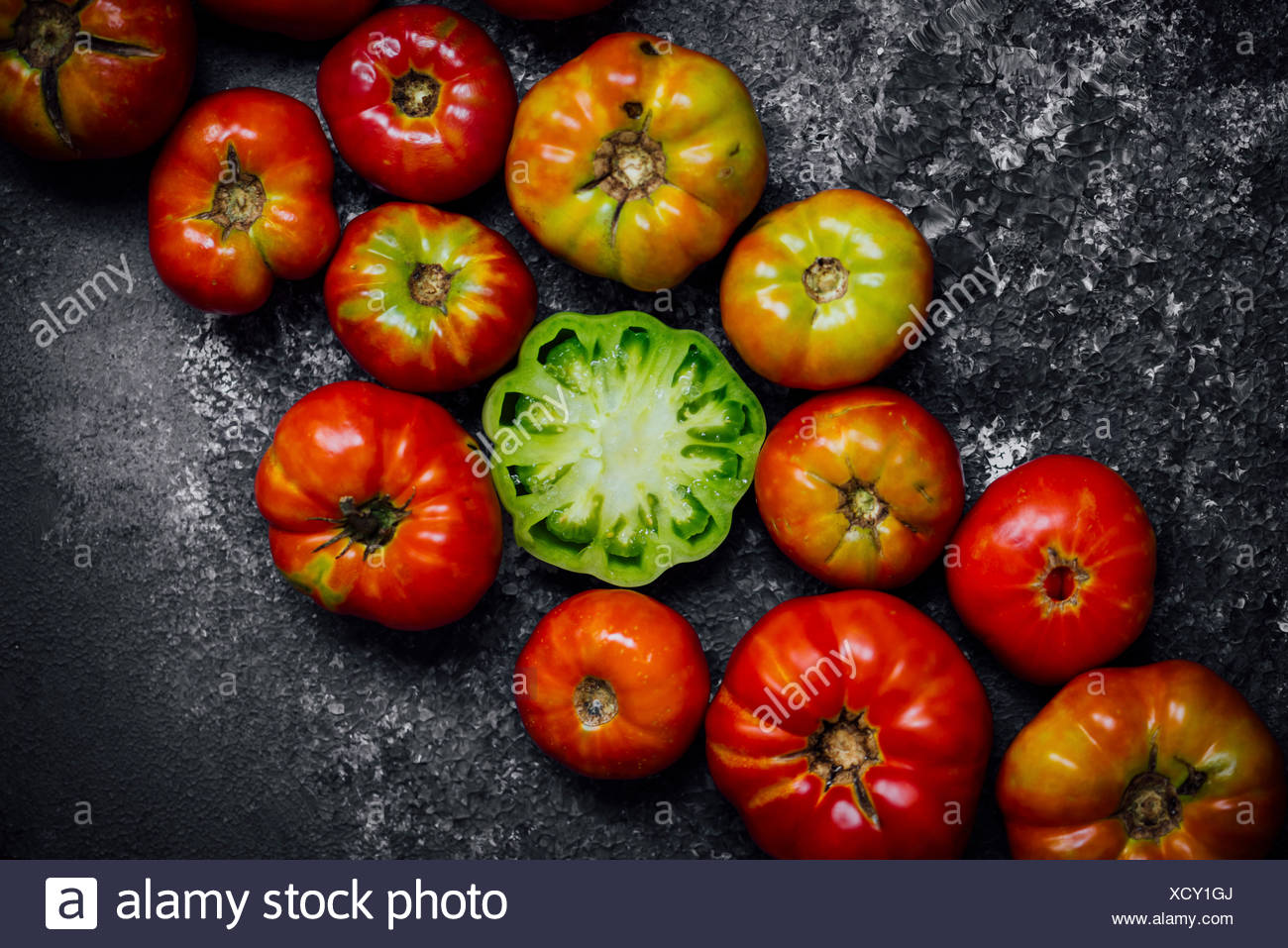 Heirloom Tomatoes gathered on a board and one halved green tomato is in the center. - Stock Image