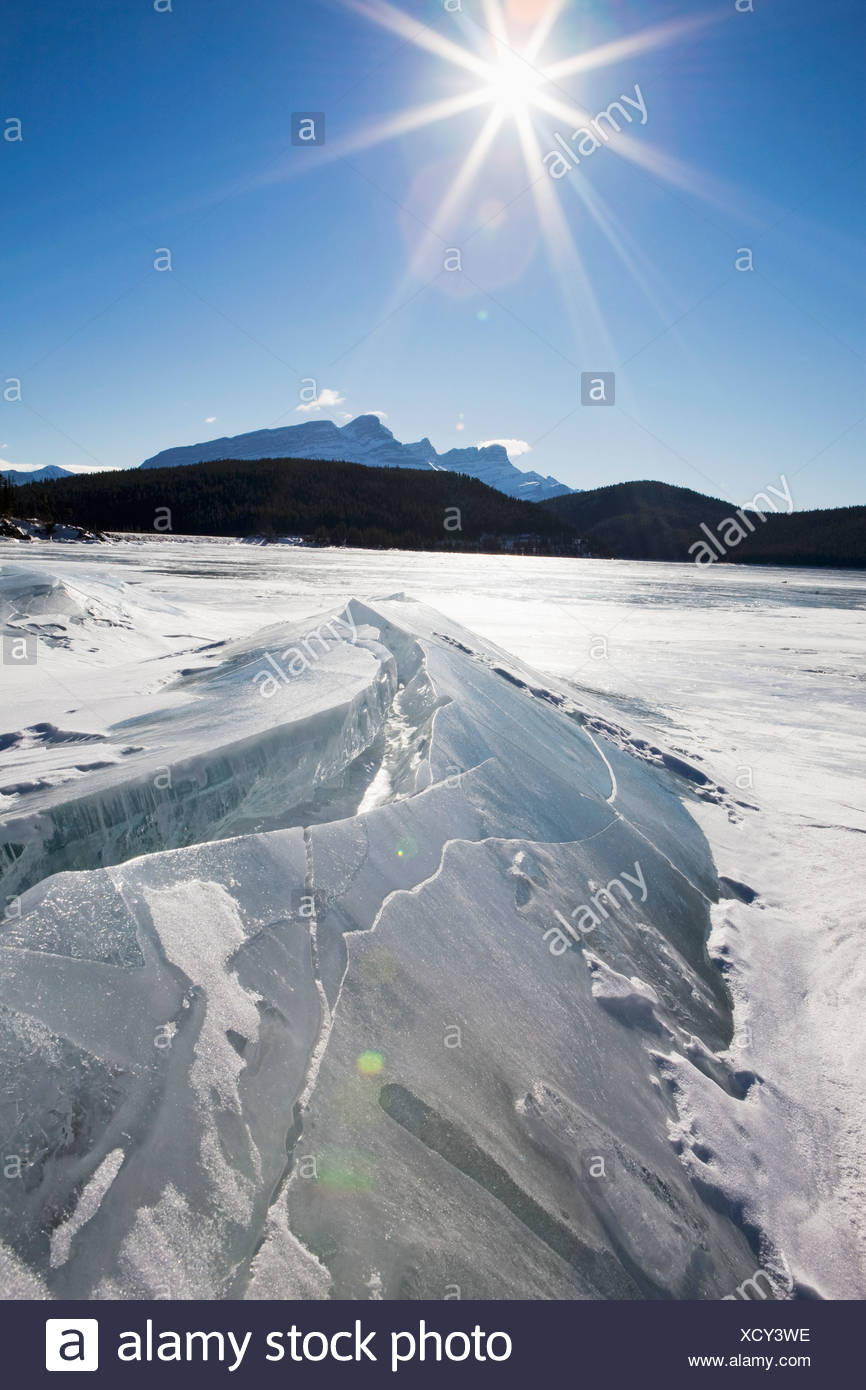 Ice Formations On A Frozen Lake Shoreline In The Mountains With A Sunburst And Blue Sky; Alberta, Canada - Stock Image