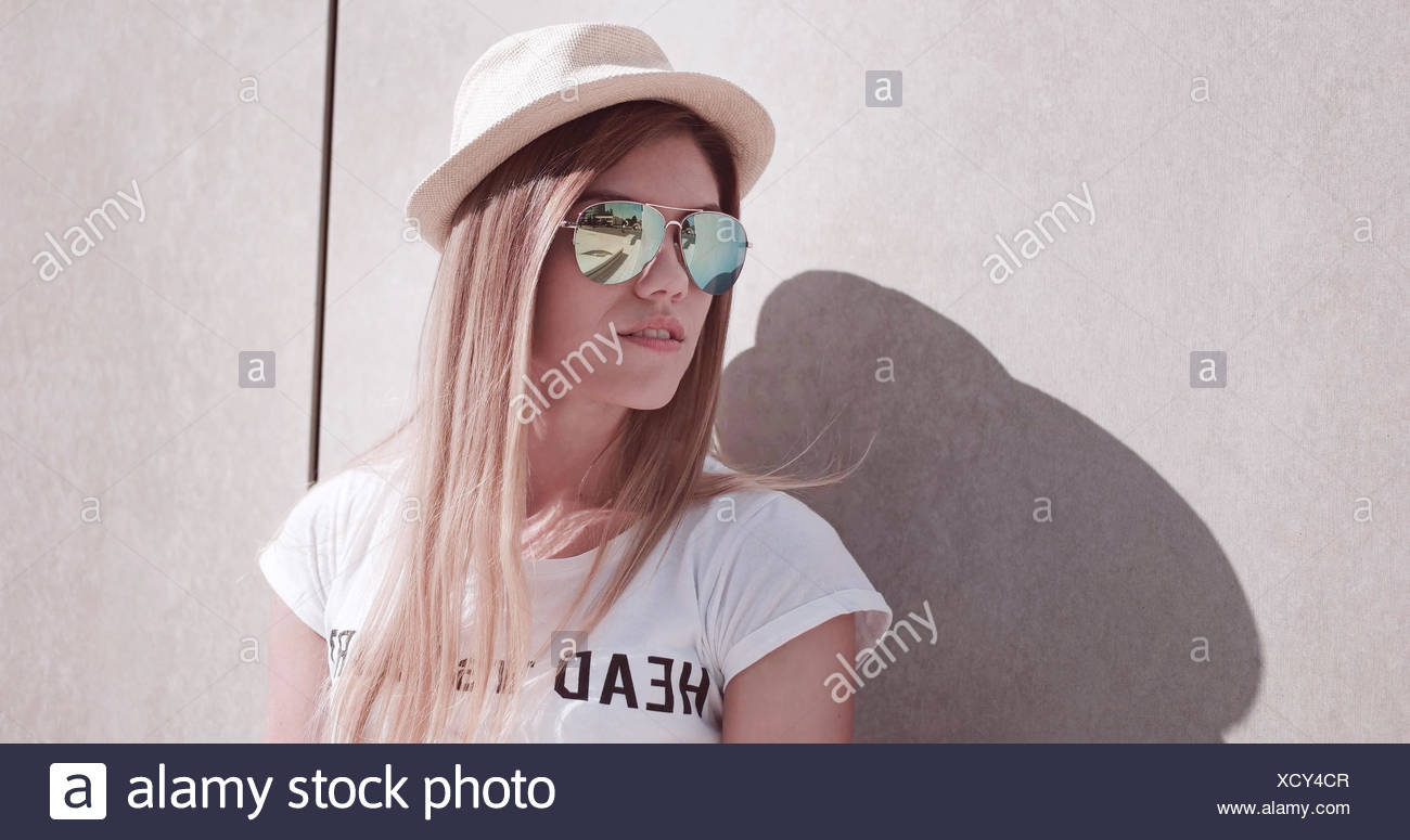 Stylish Young Woman Leaning Against The Wall Stock Photo