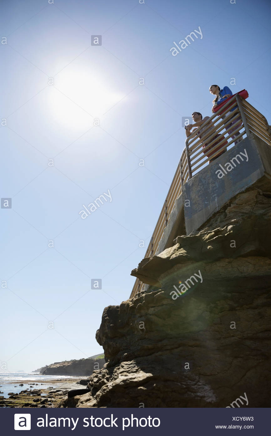 Man and woman with yoga mats on stairs above craggy sunny beach - Stock Image
