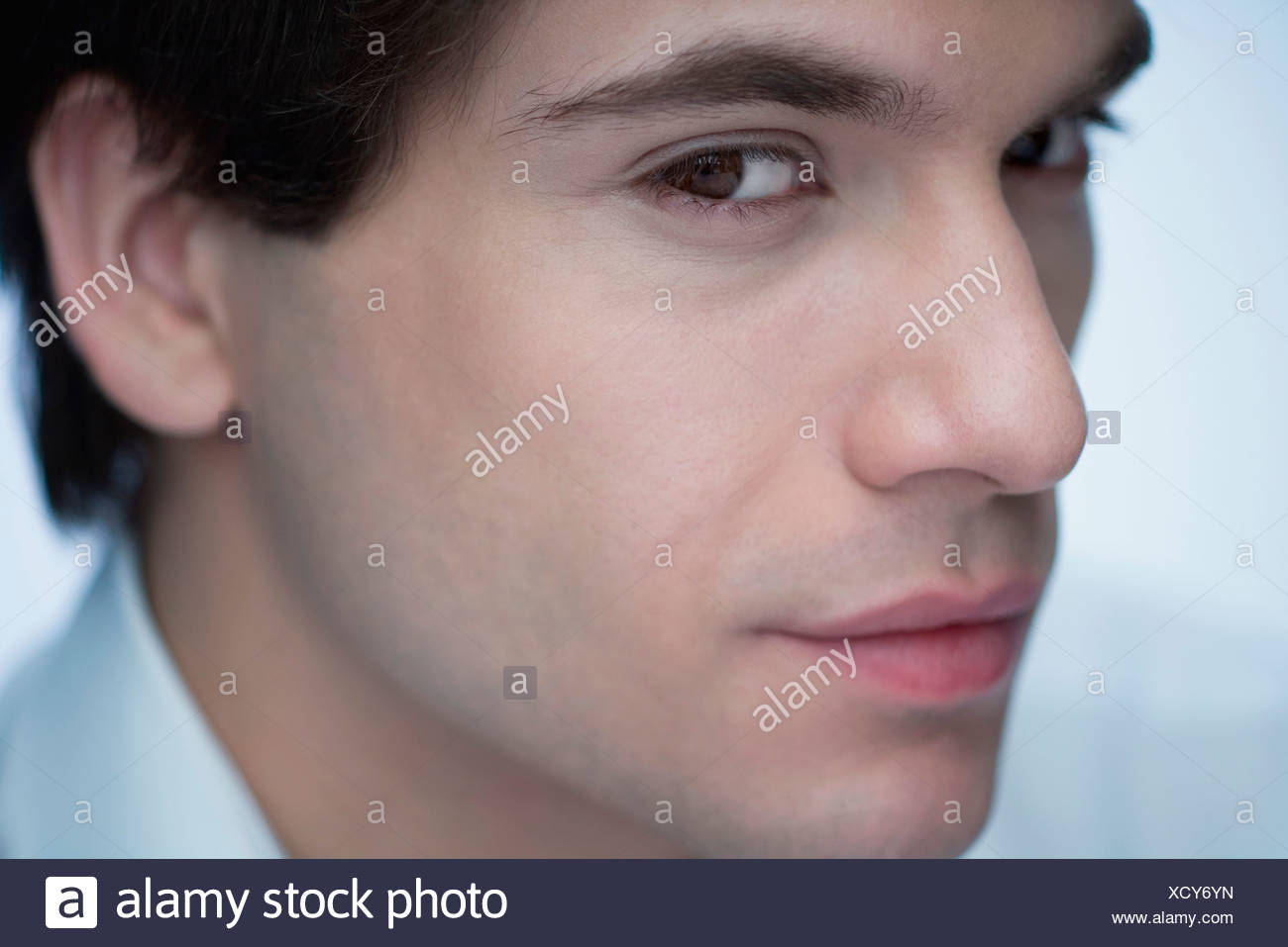Young man glancing sideways at camera, close-up - Stock Image