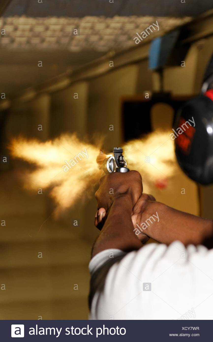 A picture taken over the shoulder of a young man firing a gun at a shooting range in the precise moment of the muzzle flash Stock Photo